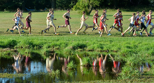 WARREN DILLAWAY / Star Beacon<br /> PARTICIPANTS IN the Ashtabula County Cross Country Meet are reflected in a pond on Tuesday at Edgewood.
