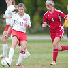 WARREN DILLAWAY / Star Beacon<br /> CARRIE POZUM (14) of Edgewood and Geneva's Summer Arndt battle for the ball Tuesday afternoon during a match at Edgewood.
