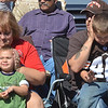 WARREN DILLAWAY / Star Beacon<br /> NANCY KUHN of Madison and her son Matthew Stancombe (right) shield the ears of Jakob Stancombe (with Nancy), 3, and Jaxin, 6, Stancombe (with Matthew), Stancombes of of Painesvile. while fire engines go  by on Saturday during the Grape Jamboree in Geneva.