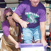WARREN DILLAWAY / Star Beacon<br /> LUCKY BORTZ of Geneva reacts to the feeling of wet grapes during the grape stomping conest Saturday at the Grape JAMboree in downtown Geneva as Laura Jones (left) assists.