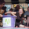 WARREN DILLAWAY / Star Beacon<br /> BONNIE PADAVICK of Euclid reacts after falling out of the bucket during the grape stomping contest Saturday at the Grape JAMboree in Geneva. Laura Jones (left) reacts during the annual event held in downtown Geneva.