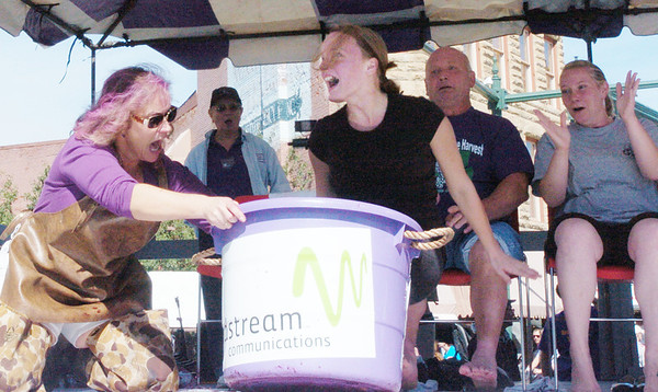 WARREN DILLAWAY / Star Beacon<br /> BONNIE PADAVICK of Euclid loses her balance during the grape stomping contest Saturday at the Grape JAMboree in Geneva. Laura Jones (left) attempts to hold the bucket steady during the annual event held in downtown Geneva.