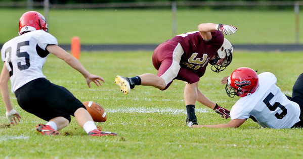 WARREN DILLAWAY / Star Beacon<br /> NICK HOLT (32) of Pymatuning Valley loses the ball as Jutin McClain (5) of Cardinal reaches for the ball and Clark Thurling (35) prepares to cover the fumble on Friday  night at Jefferson..