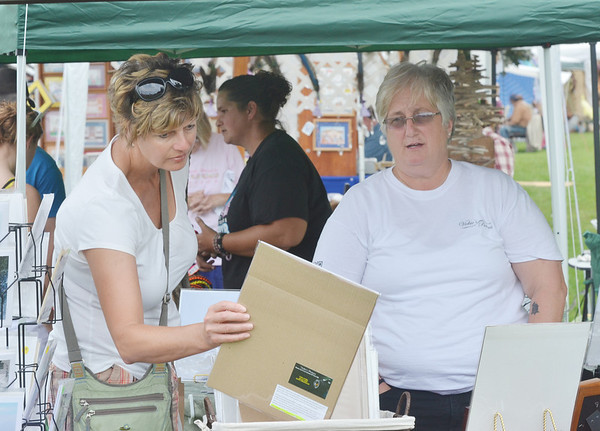 WARREN DILLAWAY / Star Beacon<br /> JANE RAMSOM of Ravenna (left) looks pictures sold by Vickie Griffin of Barberton during Crafts on the Lake at Lake Shore Park in Ashtabula Township. The event continues this morning with more than 90 vendors. It will conclude at 5 p.m.