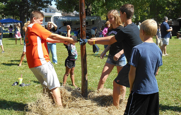 DEVASTASHA BEAVER / Star Beacon<br /> PARTICIPANTS IN the grease pole climbing contest try to create a foothold during the contest on Sunday at the Austinburg Country Days.