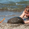 WARREN DILLAWAY / Star Beacon<br /> JORDYN RAY, 8, of Conneaut, pushes a large rock from Lake Erie during an afternoon of fun at Conneaut Township Park Thursday.