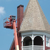 WARREN DILLAWAY / Star Beaco<br /> JEFF CONRAD of Lencl Masonry works on a chimney along Route 20 near the Cummins Road intersection on Friday. Heavy winds damaged a second chimney on the home and workers rebuilt that chimney and were doing maintenance work on this one.