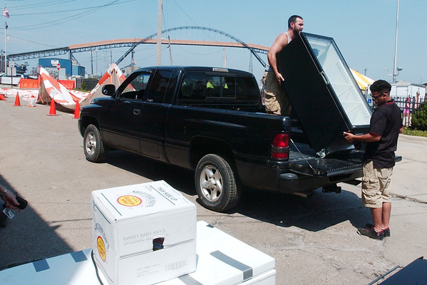 WARREN DILLAWAY / Star Beacon<br /> RICKY HERNANDEZ (top in truck) and Benny Rivera (far right) of Giant Eagle move a refrigerator from a truck as Petrick Party Rentals put up a tent in the background in preparation for the Wine and Walleye Festival this weekend on Ashtabula's Bridge Street.