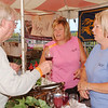 WARREN DILLAWAY / Star Beacon<br /> JOHN EMERINE (left) of Jefferson Township talks with Old Mill Winery workers Devney (center) and Sherry Peck Saturday during the Wine and Walley Fest in Ashtabula.
