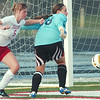 WARREN DILLAWAY / STar Beacon<br /> LEXI BAGLEY (5) of Geneva tries to kick the ball by Newton Falls goalie Stephanie Nussle Monday in Jefferson.