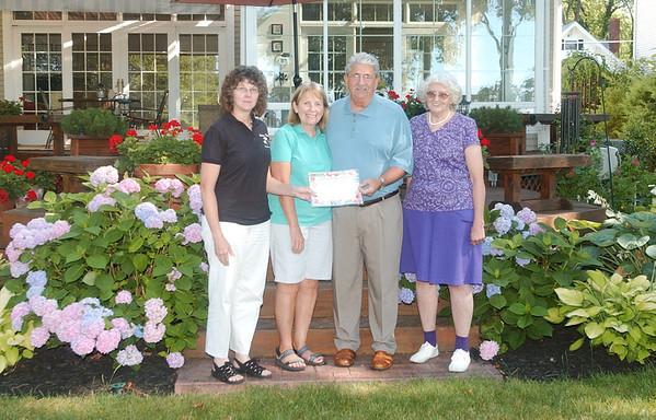 WARREN DILLAWAY / Star Beacon<br /> MARLENE AND Tom Sartini (center) receive the Garden Trails Garden Club garden of the month award from Cindi Licata, GTGC treasurer, (left) and club member Carolyn Vargo (right).