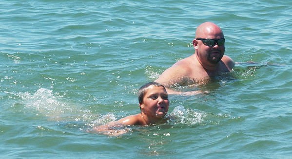WARREN DILLAWAY / Star Beacon<br /> LOGAN BRADEN, 10, and his father Scott, both of Saybrook Township, cool off in Lake Erie Monday at Walnut Beach in Ashtabula.