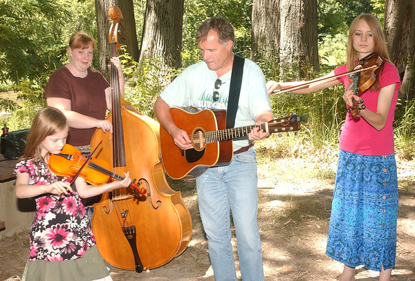 WARREN DILLAWAY / Star Beacon<br /> MEMBERS OF Young and Blue  Rick Campbell of Geneva, ( from left) Clara Klein, 7, Kelli Klein; and Deanna Klein, 17, all of Madison, practice their Blue Grass Music  on Monday at the Ashtabula County Metro Park at Harpersfield Covered Bridge.