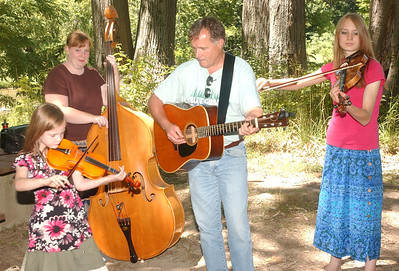 WARREN DILLAWAY / Star Beacon MEMBERS OF Young and Blue  Rick Campbell of Geneva, ( from left) Clara Klein, 7, Kelli Klein; and Deanna Klein, 17, all of Madison, practice their Blue Grass Music  on Monday at the Ashtabula County Metro Park at Harpersfield Covered Bridge.