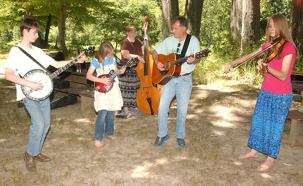 WARREN DILLAWAY / Star Beacon<br /> MEMBERS OF Young and Blue (second from right) Rick Campbell of Geneva, and (from left) Shawn Luke Klein, 13; Sylvia Klein, 10; Kelli  Klein and Deanna Klein, 17, all of Madison, practice their Blue Grass Music on Monday at the Ashtabula County Metro Park at Harpersfield Covered Bridge.