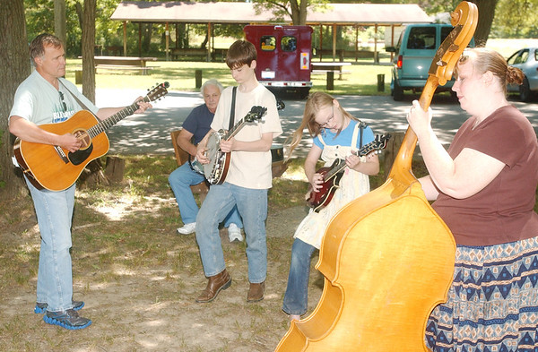WARREN DILLAWAY / Star Beacon<br /> MEMBERS OF Young and Blue (from left standing) Rick Campbell of Geneva, Shawn Luke Klein, 13; Sylvia Klein, 10, and Kelli Klein, all of Madison, practice their Blue Grass Music as Tom Petti (sitting back center) looks on Monday at the Ashtabula County Metro Park at Harpersfield Covered Bridge.