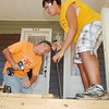 WARREN DILLAWAY / Star Beacon<br /> DANA QUINN (left) of Conneaut and Kory Kealoha, 15, of Painesville, build a new porch on a home along Main Street in Conneaut. The Loving Equally All Familes program gathered about 40 workers to help families throughout the Conneaut area.