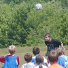 WARREN DILLAWAY / Star Beacon<br /> ZACH UTZ, a junior at Grand Valley, heads the ball while Mini Mustang soccer campers follow the play Tuesday at Orwell Community Park. The camp is run by the high school players as a fund raisesr and developmental tool for young soccer players.
