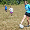 WARREN DILLAWAY / Star Beacon<br /> ASHLEY ALLMAN, a junior at Grand Valley, controls the ball while Mini Mustang soccer campers follow the play Tuesday at Orwell Community Park. The camp is run by the high school players as a fund raisesr and developmental tool for young soccer players.