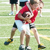 WARREN DILLAWAY / Star Beacon<br /> JACOB TOTH (with ball) and Casey Clark enjoy a drill at the Jefferson football camp at Jefferson High School Thursday morning.