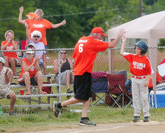 WARREN DILLAWAY / Star Beacon<br /> BRIAN MEHALIC, third base coach for the 9 and 10 All Stars, high fives Shane Gibson during a District 1 game against Geneva United at Tickner Field in Austinburg Township.