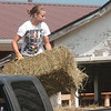 WARREN DILLAWAY / Star Beacon<br /> HEATHER PHILPOTT, 16, of Jefferson unloads hay Monday morning at the Ashtabula County Fairgrounds in Jefferson.