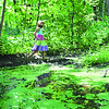CARL E. FEATHER / Star Beacon<br /> A GIRL'S colorful dress adds a splash of variety to the verdant scene in Indian Trails Park.