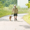 WARREN DILLAWAY / Star Beacon<br /> AL CHERRY walks with his dog Foxy along Indian Trails in the Ashtabula Township Park system near the nation's longest covered bridge. Tours of the trail area will soon be offered.