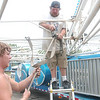 WARREN DILLAWAY / Star Beacon<br /> TYLER JOHN (left) of Ravenna works with Sam's Amusement supervisor Pete Headley of Canton. The pair were getting the Conneaut Fourth of July Festival ready to roll later today.