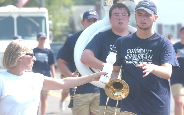 WARREN DILLAWAY / Star Beacon<br /> SUE HORVATH hands Conneaut trombone player Pat Jury a water bottle during the Conneaut Fourth of July Fesival Saturday afternoon in 90 degree heat.