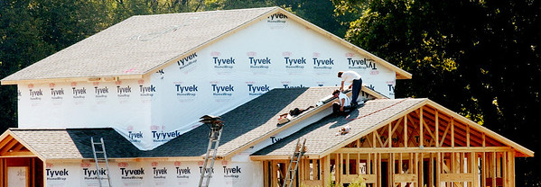 WARREN DILLAWAY / Star Beacon<br /> AN AMISH crew works on the roof of a new home on Route 6 in Andover Township.