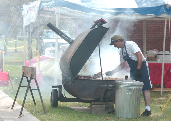 WARREN DILLAWAY / Star Beacon<br /> DONALD CLUGH, of Cunningham's Place, cooks ribs as staff of Kay's Smoking Pit (background) prepares for the Conneaut Rib Burn Off and Chill Cook Off that continues through Sunday at Conneaut Township Park.