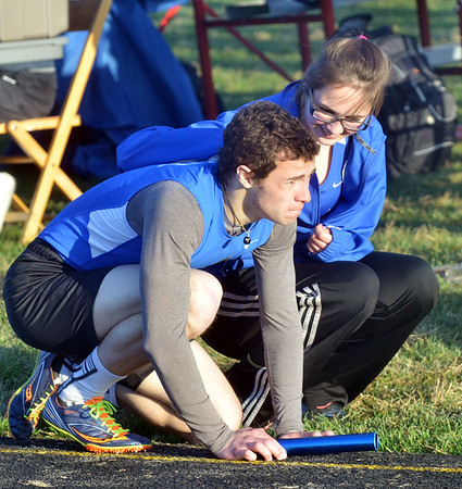 WARREN DILLAWAY / Star Beacon<br /> ELIZABETH COE of Grand Valley kneels down with Alexander White after he anchored the 4 x 800 meter relay on Friday night at the Grand Valley Twi-Light Invitational.