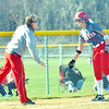 WARREN DILLAWAY / Star Beacon<br /> ELESHIA PITCHER, Geneva softball coach, congratulates Kim Brumagin as she arrives at third base on Friday in Geneva during a game with Lakeside.
