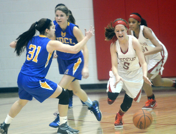 WARREN DILLAWAY / Star Beacon<br /> EMILY HARRIMAN (5) of Geneva dribbles up court as Camille Pollutro (31) of Notre Dame Cathedral Latin defends on Thursday night during a Division II sectional championship game  at Geneva.