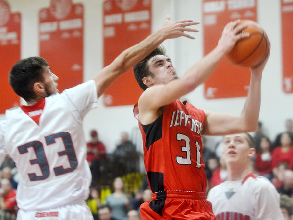WARREN DILLAWAY / Star Beacon<br /> LUCAS HITCHCOCK (31) of Jefferson drives to the basket as Eli Kalil (33) of Edgewood defends on Tuesday night at Edgewood.