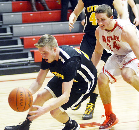 WARREN DILLAWAY / Star Beacon<br /> AUSTIN HESS of Riverside loses the ball out of bbounds as Zac Sweat of Geneva (14) defends on Friday night at Geneva.