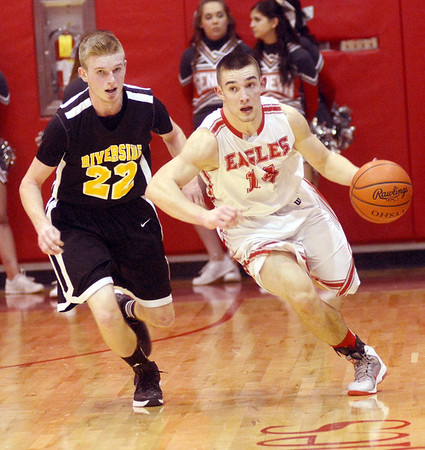 WARREN DILLAWAY / Star Beacon<br /> ZAC SWEAT (with ball) of Geneva dribbles up court with Austin Hess (22)  of  Riverside in hot pursuit on Friday night at  Geneva.