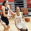 WARREN DILLAWAY / Star Beacon<br /> LINDSEY MAYLE (13) of Geneva drives by Sara Price of Howland on Saturday at Geneva.
