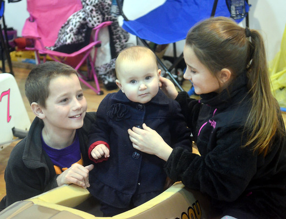 WARREN DILLAWAY / Star Beacon<br /> DANNY THOMPSON (left) and Mikayla Thompson (right), both of Conneaut put Amelia Scalise in a car during the Northeast Ohio Soap Box Derby Rally Race at Ashtabula Towne Square in Ashtabula Township.