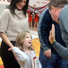 WARREN DILLAWAY / Star Beacon<br /> MAGGIE HOZA  prepares to high five Edgewood High School Athletic Director Steve Kray as Hoza's mother Daniellle watches on Friday evening during a scoreboard dedication at the school's gymnasium. The Hoza's were representing The Healthy Smile Center, one of five businesses, that hhelped make the $10,000 project a realty.