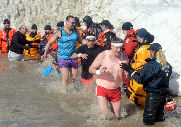 WARREN DILLAWAY / Star Beacon<br /> PARTICIPANTS IN the Polar Bear Plunge dash from the cold waters of Lake Erie on Saturday afternoon at Geneva State Park.