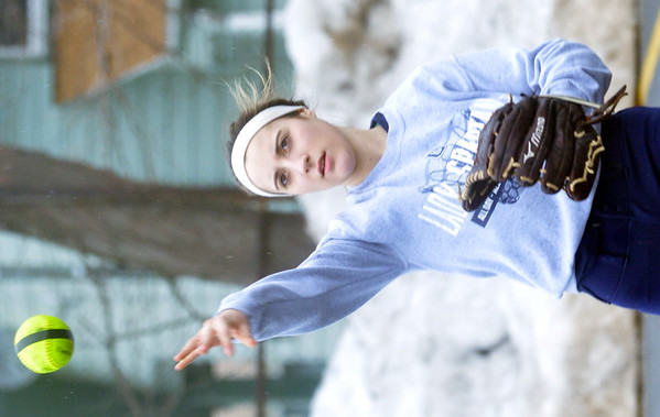 WARREN DILLAWAY / Star Beacon<br /> LEXI CAMPBELL throws in front of a wall of snow during Conneaut High School softball practice on Monday in the school's parking lot.