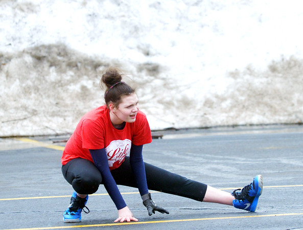 WARREN DILLAWAY / Star Beacon<br /> TULLY TAYLOR stretches in front of a wall of snow during Conneaut High School softball practice on Monday in the school's parking lot.