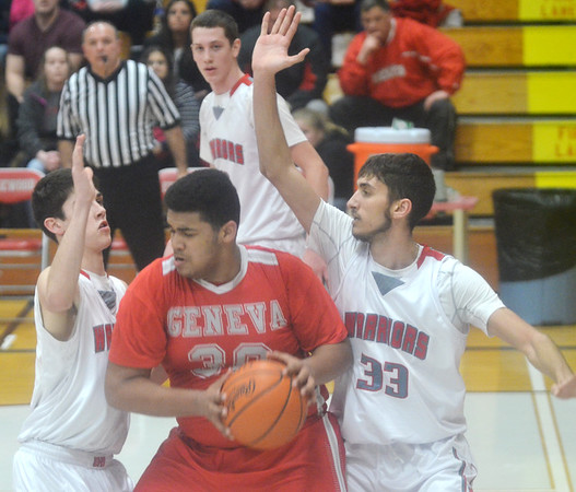 WARREN DILLAWAY / Star Beacon<br /> TRAYVON MILLER (with ball) of Geneva is surrounded by Edgewood defenders Justin Searles (left), Eli Kalil (right)  and Marcus Ernst (background) on Tuesday night during a Division II sectional semifinal game at Edgewood.