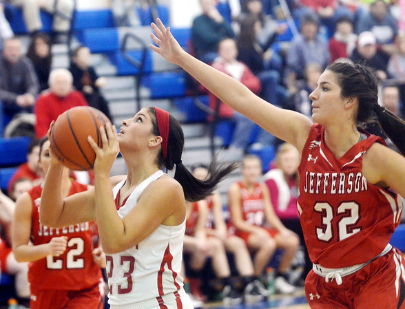 WARREN DILLAWAY / Star Beacon<br /> SARAH JUNCKER of Geneva drives to the basket as Kaycee Fusco (32) of Jefferson defends during the Division II District championship game at Grand Valley on Thursday evening.