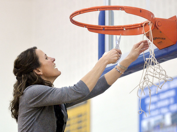 WARREN DILLAWAY / Star Beacon<br /> GENEVA GIRLS basketball coach Nancy Barbo cuts down the net after defeating Jefferson to win the Division II district championship on Thursday night in Orwell.