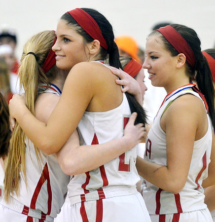 WARREN DILLAWAY / Star Beacon<br /> SARAH JUNCKER (center) hugs Geneva teammate Alex Schafer as Lindsey Mayle (right) watches during the team celebration after defeating Jefferson during th edivvision II District championship game.