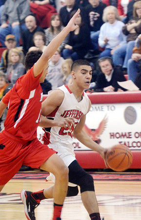 WARREN DILLAWAY / Star Beacon<br /> JAMES JACKSON (25) of Jefferson dribbles up court as David Holbert (10) of  Harvey defends on Friday night during a Division II sectional championship game at Jefferson.