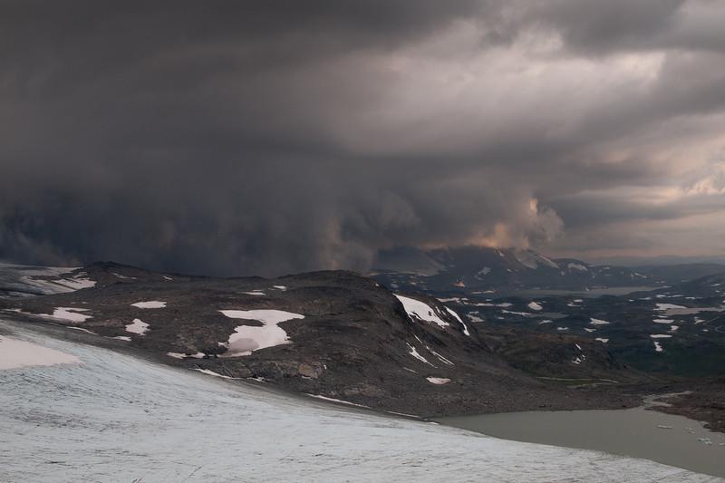 Storm clouds gather over Hurrungane mountain range. Seen from Store Smørstabbtind. Jotunheimen National Park. Norway.
